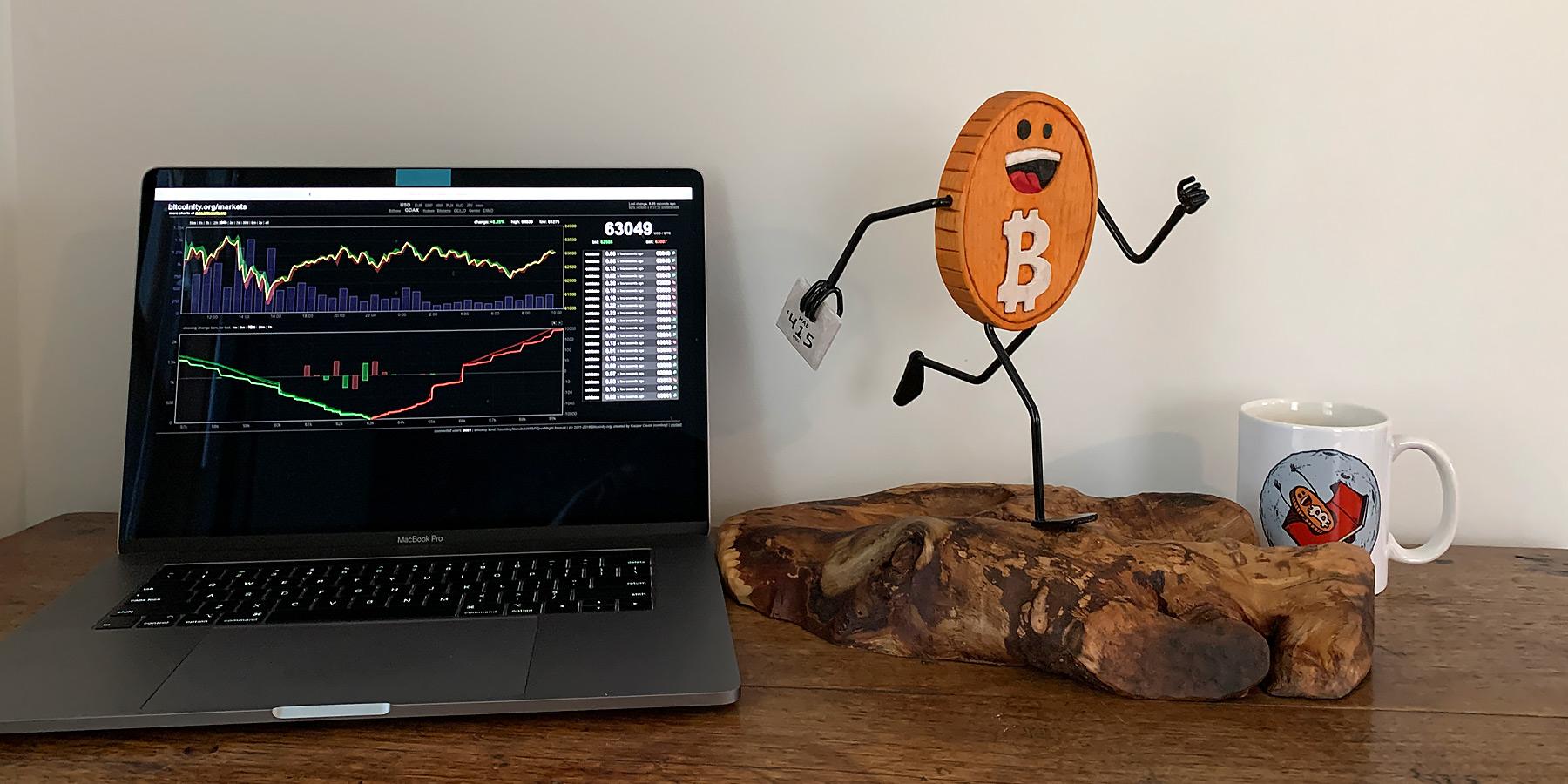 Running Bitcoin sculpture with computer and mug